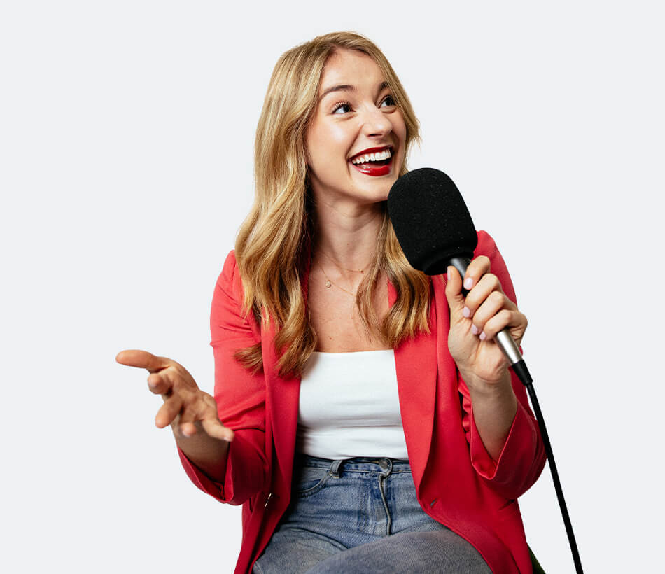 Annelise on pink blouse sitting and smiling while holding a microphone